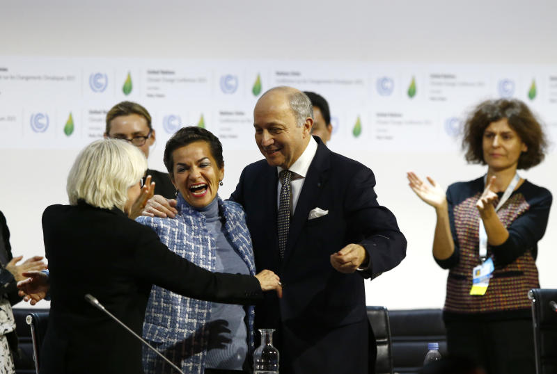 FILE - In this Dec. 12, 2015 file photo, French foreign minister and President of the COP21 Laurent Fabius, center, hugs France's Laurence Tubiana, special representative for the COP21, left, and United Nations climate chief Christiana Figueres after the final conference of the COP21, the United Nations conference on climate change, in Le Bourget, north of Paris. The international effort to fight climate change is about to get injected with a bit of Hollywood flash, a lot of Wall Street green and a considerable dose of cheerleading rather than dry treaty negotiations. Business leaders, mayors, governors and activists from around the world gather Wednesday, Sept. 12, 2018, in San Francisco for the Global Climate Action Summit, where participants will trumpet what they've done and announce new efforts to slow a warming world. (AP Photo/Francois Mori, File)