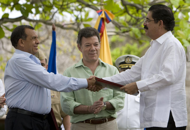 Honduras' President Porfirio Lobo, left, and Honduras' ousted President Manuel Zelaya, right, shake hands after signing an agreement as Colombia's President Juan Manuel Santos applauds in Cartagena, Colombia, Sunday, May 22, 2011. The accord allows the return of Zelaya to his homeland and Honduras' re entry into  the Organization of American States, OAS, as a solution to the crisis caused by the June 2009 coup that sent Zelaya into exile and caused the OAS to suspend Honduras as a member. (AP Photo/William Fernando Martinez)