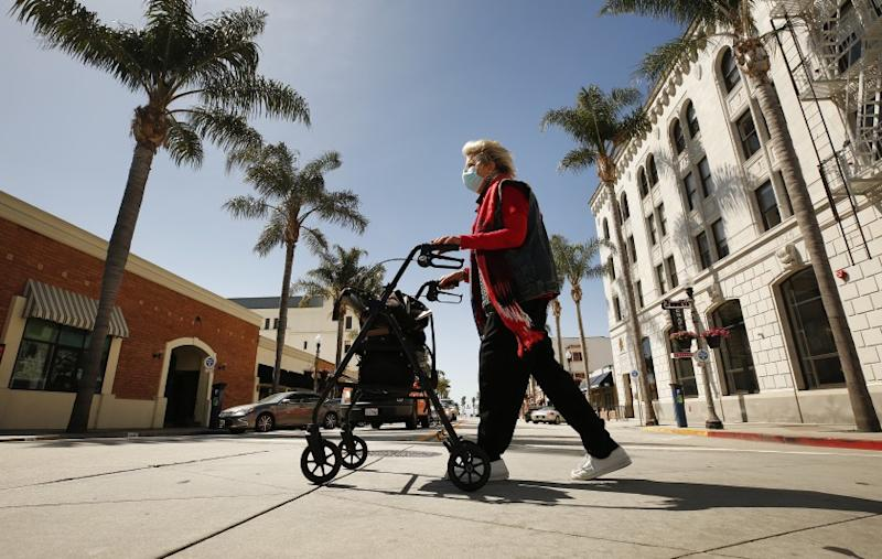 """VENTURA, CA - APRIL 22: Local historian Cynthia Thompson crosses South California Street on East Main in downtown Ventura Wednesday morning as Ventura County on Saturday modified its stay-at-home order to permit some businesses to reopen and some gatherings to take place for the first time since the restrictions were issued to fight the spread of the coronavirus COVID-19. Cynthia said """"I think this is absolutely necessary. It's exactly like the plague of 1918. Mandatory masks, closing everything down, and they used churches as hospitals."""" """"You have to give people hope, but you have to be very cautious. It's an invisible enemy."""" She added. Ventura on Wednesday, April 22, 2020 in Ventura, CA. (Al Seib / Los Angeles Times)"""