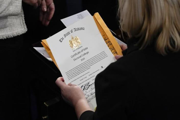 The certification of Electoral College votes for the state of Alabama is unsealed during a joint session of the House and Senate convenes to confirm the electoral votes cast in November's election, at the Capitol, Wednesday, Jan 6, 2021. (AP Photo/Andrew Harnik)