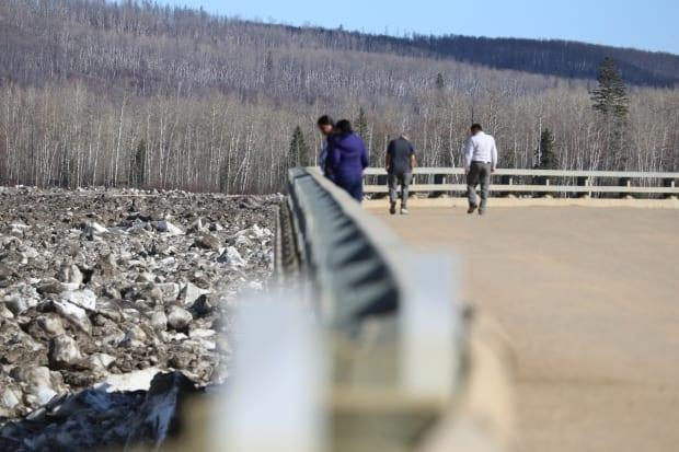 People stand on the side of the highway in Fort McMurray during the April 2020 flood.