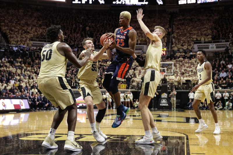 Virginia forward Mamadi Diakite (25) is stripped of the ball by Purdue guard Sasha Stefanovic (55), between Purdue's Trevion Williams (50) and Matt Haarms during the first half of an NCAA college basketball game in West Lafayette, Ind., Wednesday, Dec. 4, 2019. (AP Photo/Michael Conroy)