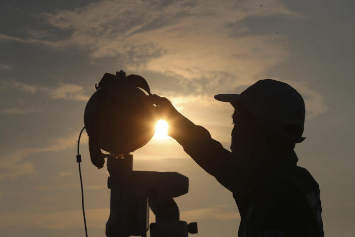 An official is silhouetted as he uses a telescope to scan the horizon for a crescent moon that will determine the beginning of the holy fasting month of Ramadan in Jakarta, Indonesia, Monday, April 12, 2021.(AP Photo/Achmad Ibrahim)