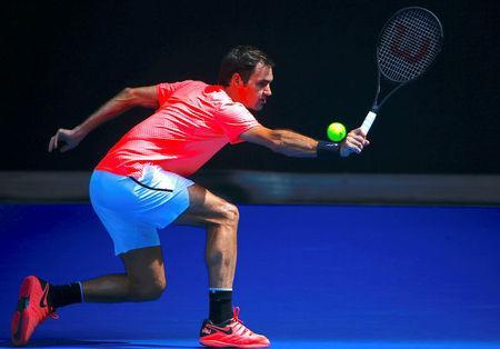 Switzerland's Roger Federer stretches to hit a shot during a practice session on Rod Laver Arena ahead of the Australian Open tennis tournament. REUTERS/David Gray