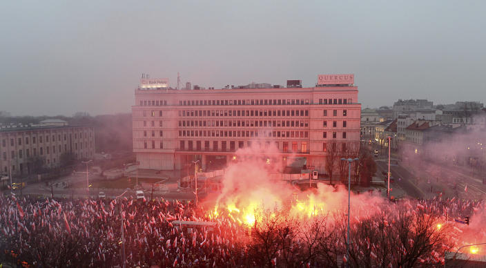 Marchers burn flares in the annual March of Independence organized by far right activists to celebrate 100 years of Poland's independence, in Warsaw, Sunday Nov. 11, 2018. The nation of Poland regained its sovereignty at the end of World War I after being wiped off the map for more than a century. (AP Photo/Alik Keplicz)