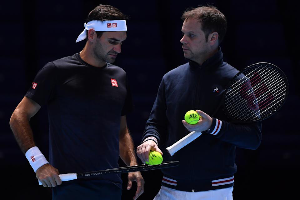 Roger Federer and coach Severin Luthi talk during practice.