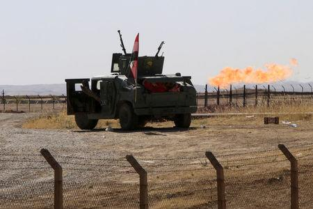 FILE PHOTO: Flames emerge from flare stacks at the oil fields in Dibis area on the outskirts of Kirkuk