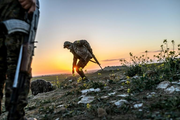 The sun sets as Syrian Democratic Forces fighters keep watch on a hilltop near the embattled village of Baghouz