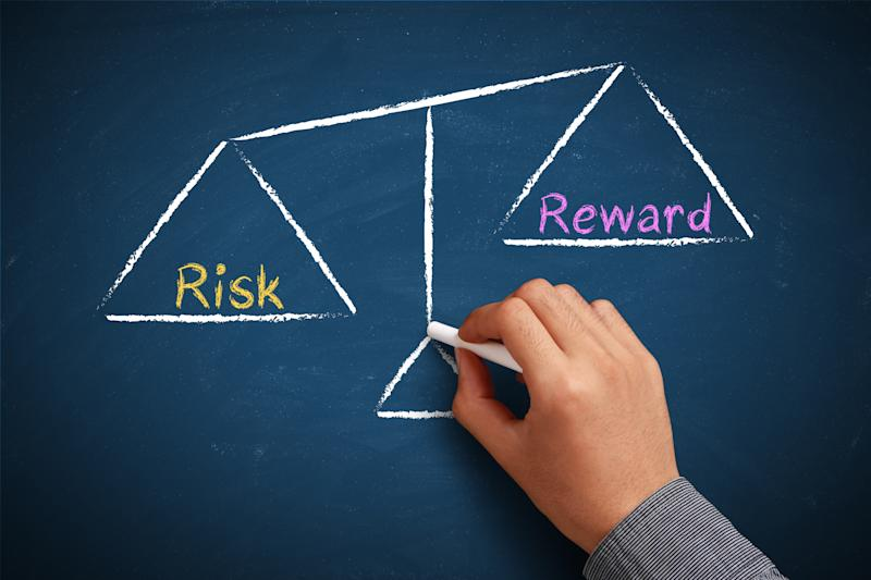 A hand drawing a risk versus reward scale