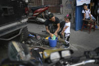 Motorcycle stuntman Pedro Aldana cleans motorcycle parts with his daughter Alanis as his young neighbor and admirer, 6-year-old Milan Sandoval Ramos, watches from a chair outside their home in the Catia neighborhood of Caracas, Venezuela, Thursday, Jan. 21, 2021. Of Aldana's two children, 4-year-old Alanis is the only one interested in his work, who he plans to teach her how to ride a motorcycle. (AP Photo/Matias Delacroix)
