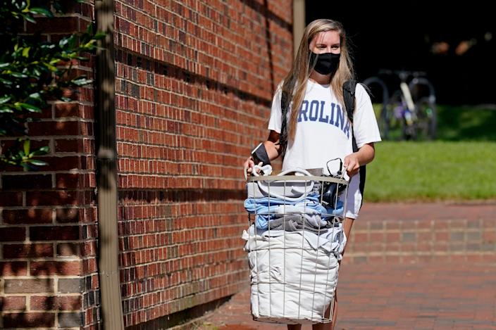 """Freshman Sarah Anne Cook carries her belongings as she packs to leave campus following a cluster of COVID-19 cases at the University of North Carolina in Chapel Hill, North Carolina. <p class=""""copyright"""">AP Photo/Gerry Broome</p>"""