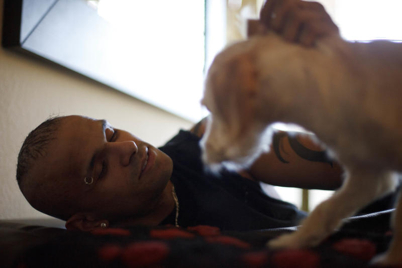 In this April 24, 2012 image, former Marine Christian Ellis, 29, plays with his dog in his apartment in Denver. The former Marine machine gunner, who has attempted suicide four times, is putting his pain on stage in the first opera believed written about the Iraq War. (AP Photo/Gregory Bull)
