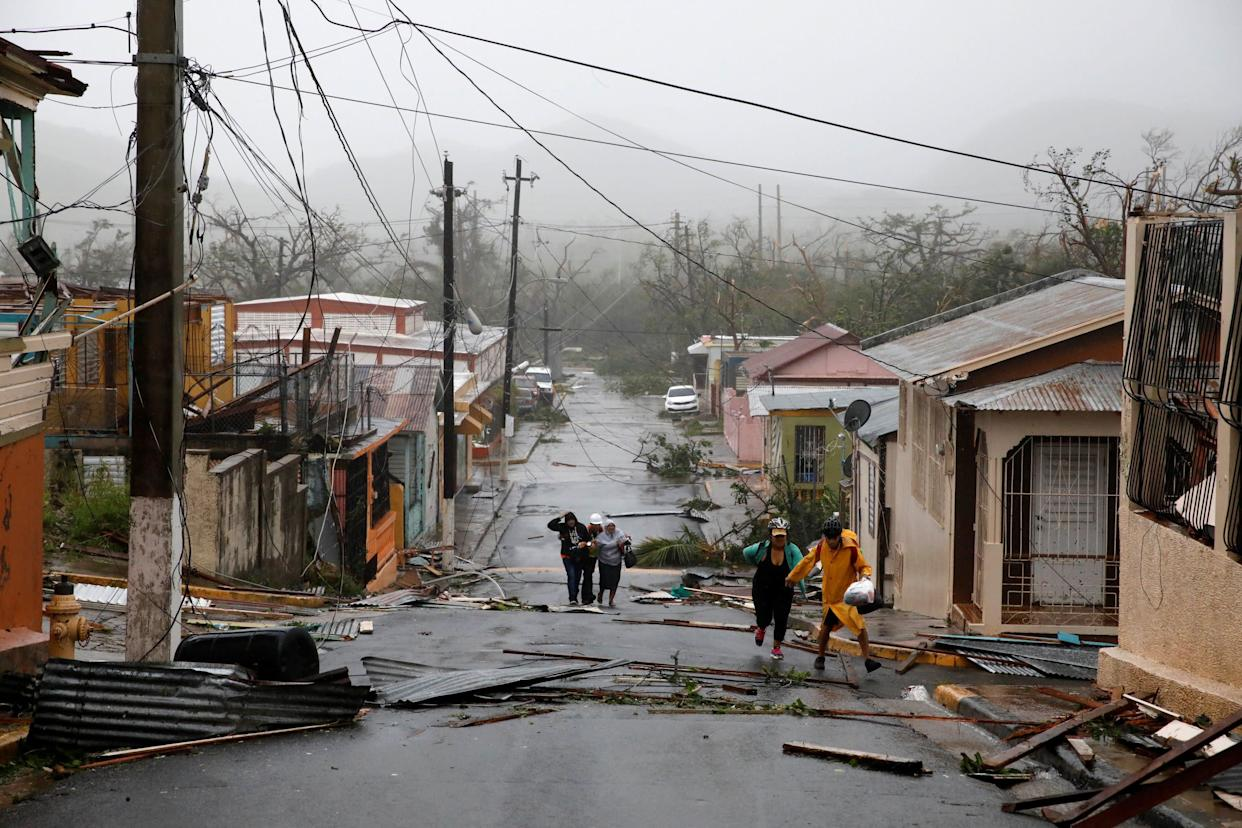 Rescue workers help people after the area was hit by Hurricane Maria.