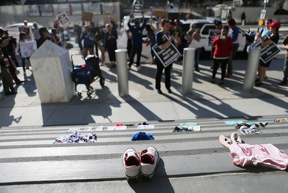 Protestors demonstrate against the separation of migrant children from their families in front of clothes representing migrant children on June 18, 2018 in Los Angeles, California. U.S. Immigration and Customs Enforcement arrested 162 undocumented immigrants last week during a three-day operation in Los Angeles and surrounding areas. (Photo by Mario Tama/Getty Images)