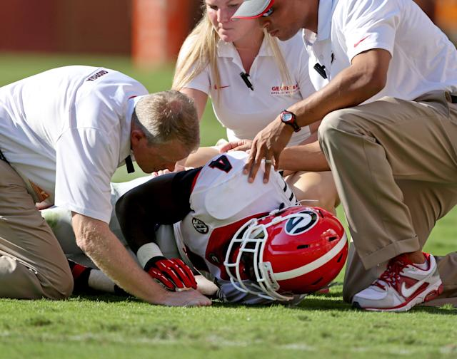Georgia trainers talk with Georgia's Keith Marshall (4) after he was injured in the first half of an NCAA college football game in Knoxville, Tenn., Oct. 5, 2013. (AP Photo/Atlanta Journal-Constitution, Jason Getz)