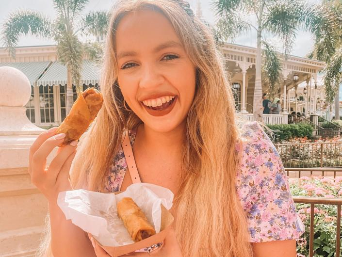 kayleigh price holding a cheeseburger egg roll at magic kingdom in disney world