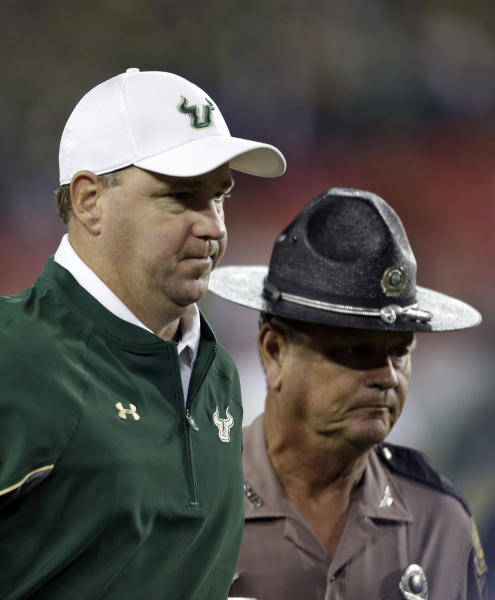 South Florida head coach Skip Holtz is escorted off the field after losing to Pittsburgh 27-3 during an NCAA college football game Saturday, Dec. 1, 2012, in Tampa, Fla. (AP Photo/Chris O'Meara)