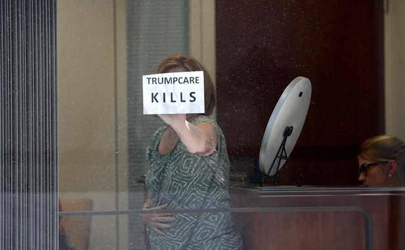 A healthcare activist holds up a sign while she and others occupy the office of Sen. Dean Heller (R-Nev.) to protest the Republican health care bill at the U.S. Capitol on July 10, 2017.
