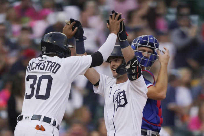 Detroit Tigers' Zack Short, center, is greeted at home by teammate Harold Castro after they both scored on Short's two-run home run during the second inning of a baseball game against the Texas Rangers, Wednesday, July 21, 2021, in Detroit. (AP Photo/Carlos Osorio)