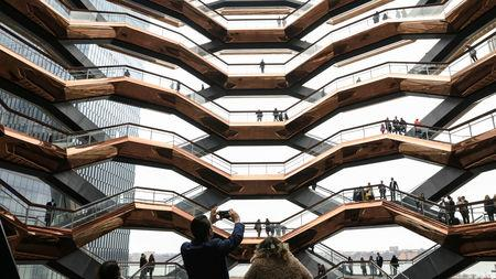 People tour the inside 'The Vessel,' a large public art sculpture made up of 155 flights of stairs, during the grand opening of the The Hudson Yards development, a residential, commercial, and retail space on Manhattan's West side in New York City, New York, U.S., March 15, 2019. REUTERS/Brendan McDermid