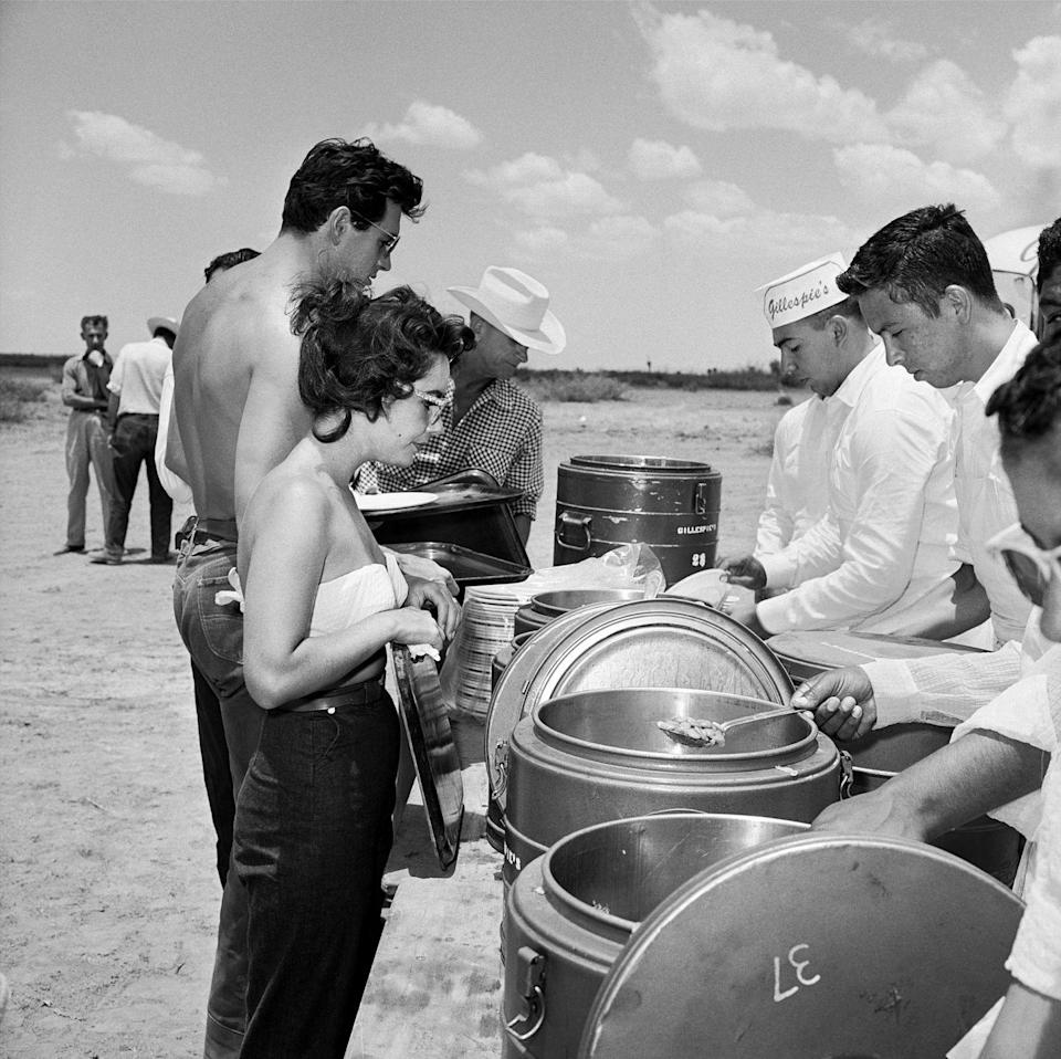 <p>Elizabeth Taylor and Rock Hudson make their way through the buffet line during the lunch line on the set of Giant. </p>
