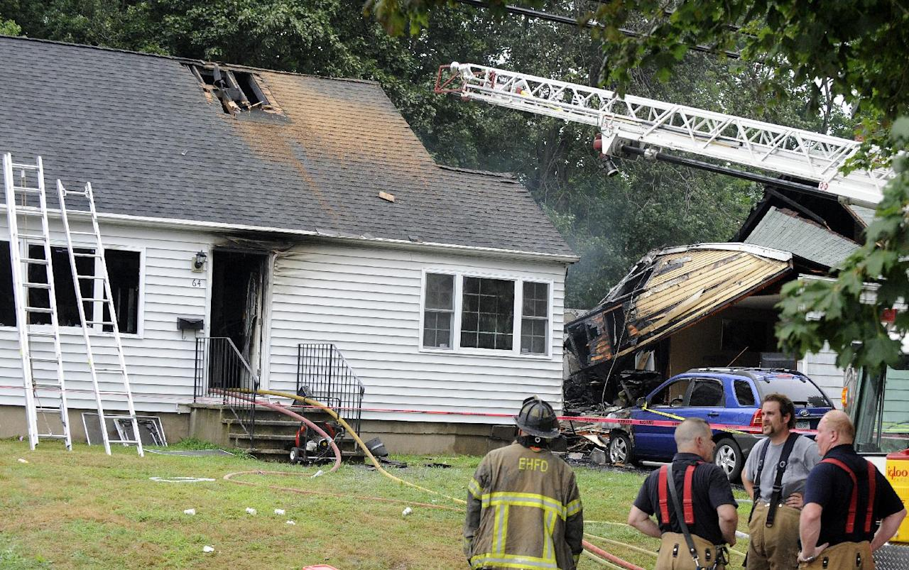 Firefighters stand at the scene of a plane crash, Friday, Aug. 9, 2013, in East Haven, Conn. The multi-engine, propeller-driven plane plunged into a working-class suburban neighborhood near Tweed New Haven Airport, on Friday. (AP Photo/Fred Beckham)
