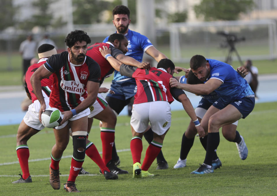 UAE's player runs with the ball against Israel players during a friendly match in Dubai, United Arab Emirates, Friday, March 19, 2021. (AP Photo/Kamran Jebreili)