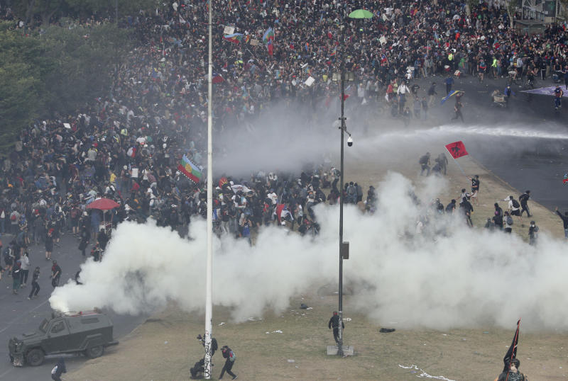 Police spray tear gas and water during an anti-government protest in Santiago, Chile, Monday, Nov. 4, 2019. Chile has been facing weeks of unrest, triggered by a relatively minor increase in subway fares. The protests have shaken a nation noted for economic stability over the past decades, which has seen steadily declining poverty despite persistent high rates of inequality. (AP Photo/Esteban Felix)