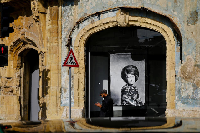 In this Nov. 27, 2018, photo, a man passes in front of Beit Beirut, the nearly 100 year-old house that served as a sniper position during Lebanon's 1975-1990 civil war, on a former Beirut frontline, Lebanon. Nearly 30 years after civil war guns fell silent, dozens of bullet-scarred, shell-pocked buildings are still standing _ testimony to a brutal conflict that raged for 15 years and took the lives of 150,000 people. (AP Photo/Hassan Ammar)