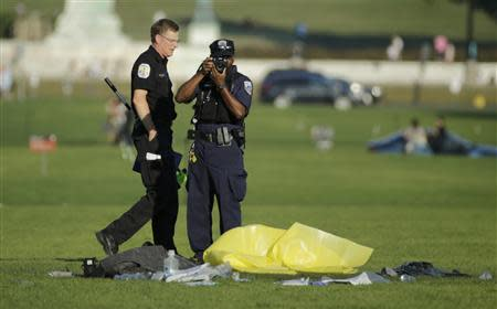 Police officers investigate the scene where a man set himself on fire in front of the U.S. Capitol on the U.S. National Mall in Washington