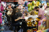 People meet a booth looking to buy items on the final day of the convention floor at the ASD Market Week convention Wednesday, Aug. 25, 2021, in Las Vegas. In pre-COVID times, business events like conferences and trade shows routinely attracted more than 1 billion participants and $1 trillion in direct spending each year. The pandemic brought those gatherings to a sudden halt, but now in-person meetings are on the rebound from Las Vegas to Beijing. (AP Photo/John Locher)