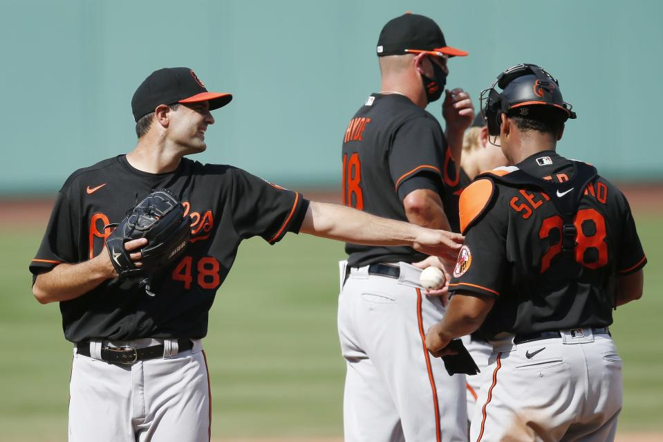Baltimore Orioles' Richard Bleier (48) walks off the mound and reaches out to Pedro Severino (28) after being relieved by manager Brandon Hyde (18) during the eighth inning of a baseball game against the Boston Red Sox, Saturday, July 25, 2020, in Boston. (AP Photo/Michael Dwyer)