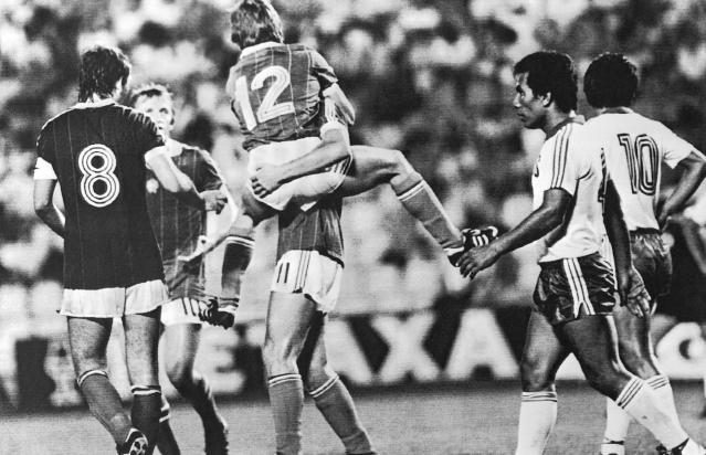 FILE - In this June 15, 1982 file photo, Hungary's Laszlo Fazekas, center, jumps on Gabor Poloskei, after scoring the third goal for his country, during the World Cup soccer match between Hungary and El Salvador, in Elche, Spain. Hungary's Tibor Nyilasi, stands at left. Hungary defeated El Salvador 10-1. (AP Photo/File)