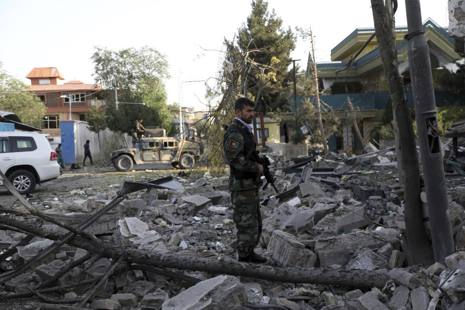 An Afghan security person stands amid debris from a damaged building following an attack in Kabul, Afghanistan, Wednesday, Aug. 4, 2021. A powerful explosion rocked an upscale neighborhood of Afghanistan's capital Tuesday in an attack that apparently targeted the country's acting defense minister. (AP Photo/Rahmat Gul)