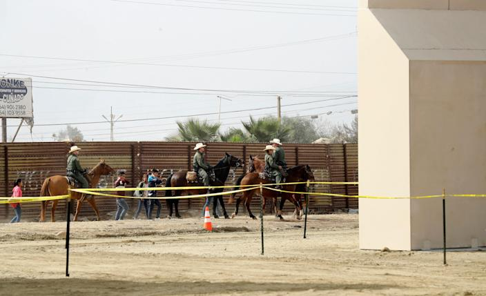 On Oct. 19, 2017, a group of people are detained by Border Patrol agents on horseback after crossing the border illegally from Tijuana, Mexico, near where prototypes for a border wall, right, were being constructed in San Diego.