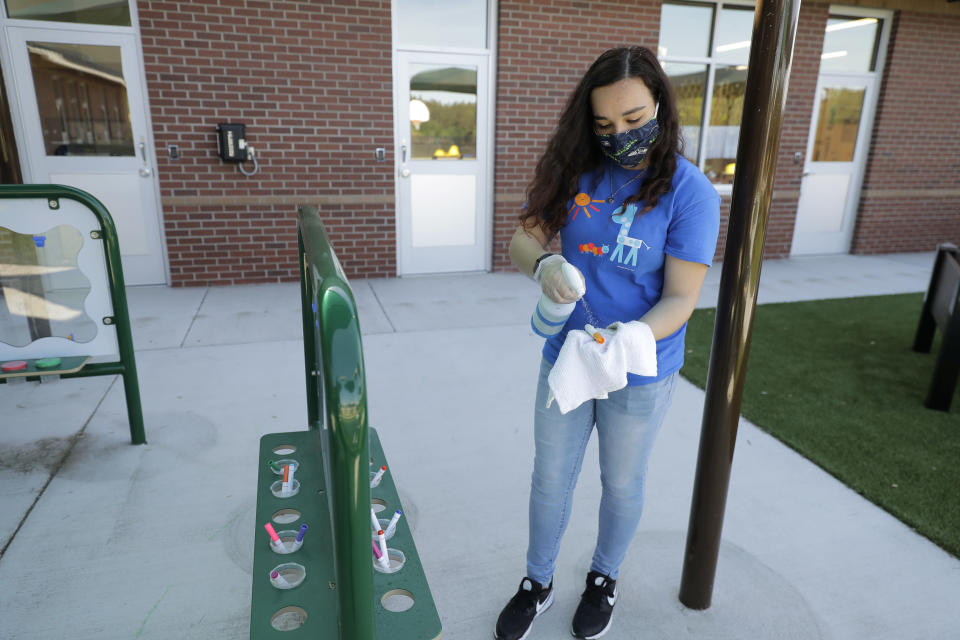 In this May 27, 2020 photo, Alena Kleinman, a worker at the Frederickson KinderCare daycare center in Tacoma, Wash., wears a mask as she cleans a marker used at an outdoor art station following use by a class, a task that is repeated several times a day. In a world weary of the coronavirus, many working parents with young children are now struggling with the decision on when or how they'll be comfortable returning to their child care providers. Frederickson KinderCare has been open throughout the pandemic to care for children of essential workers. (AP Photo/Ted S. Warren)