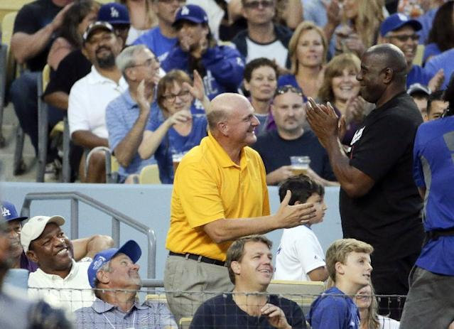 New Los Angeles Clipper owner Steve Ballmer, left, is greeted by Magic Johnson after he was shown on big screen during first inning of a baseball game between the Los Angeles Dodgers and the San Diego Padres in Los Angeles, Tuesday, Aug. 19, 2014. (AP Photo/Chris Carlson)