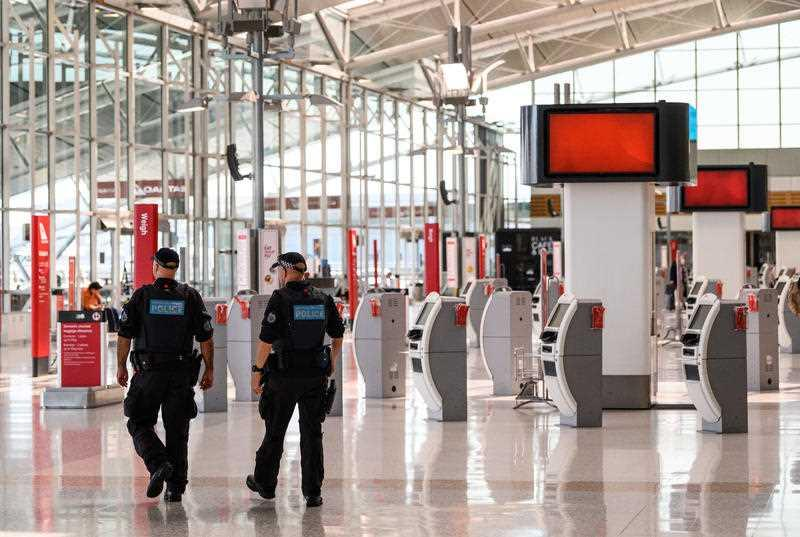 Police walk through an empty Sydney Airport.