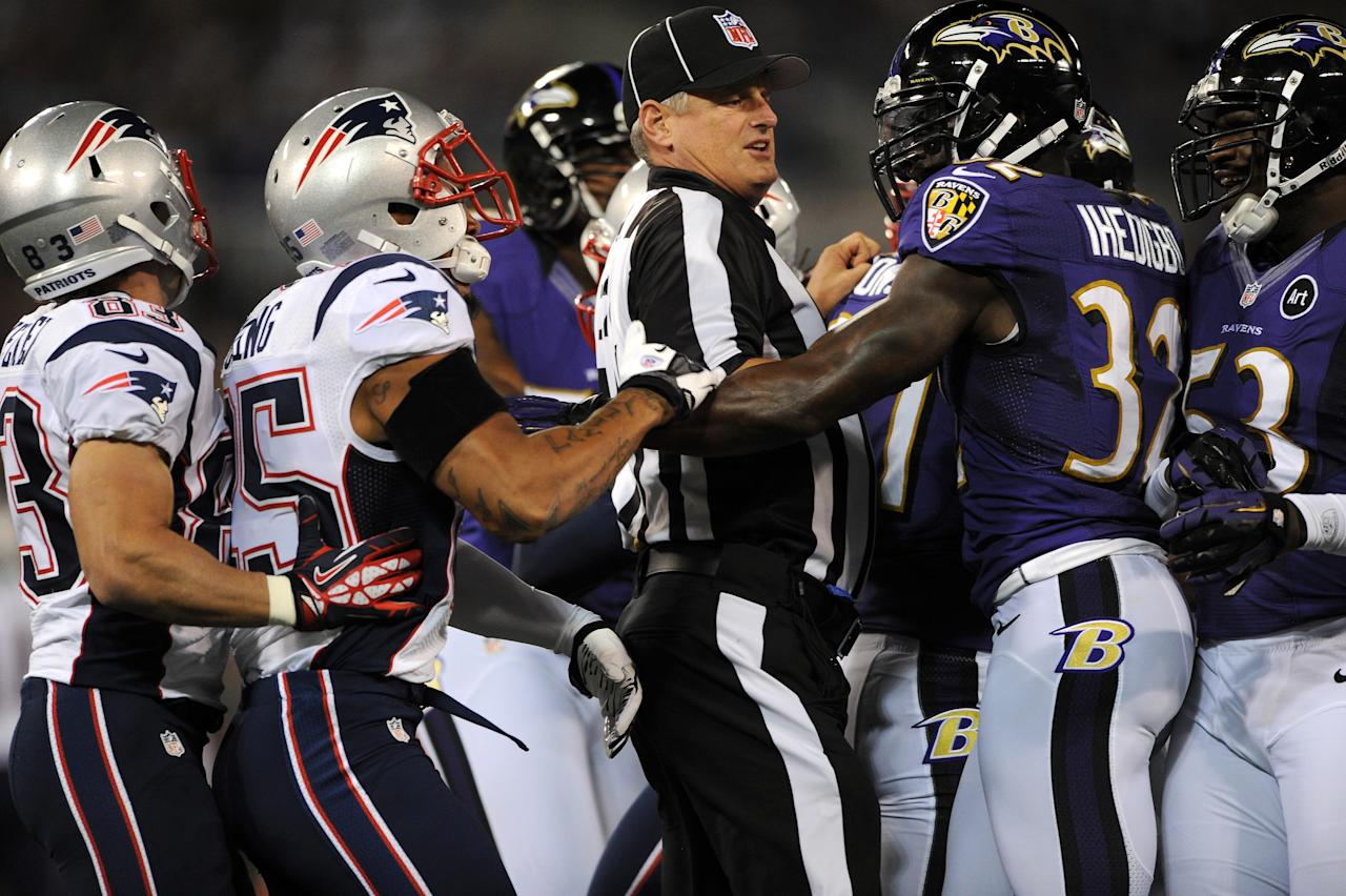 BALTIMORE, MD - SEPTEMBER 23: A referee seperates players from the New England Patriots and the Baltimore Ravens in the first half at M&T Bank Stadium on September 23, 2012 in Baltimore, Maryland. (Photo by Patrick Smith/Getty Images)