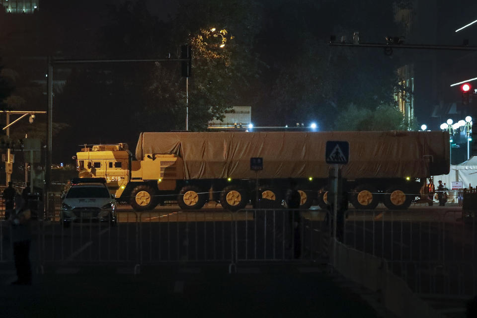 In this Saturday, Sept. 21, 2019, photo, a Chinese military vehicle carrying a covered-up ballistic missile passes along the Jianguomenwai Avenue during a rehearsal for the 70th anniversary of Communist China, in Beijing. A parade on Tuesday, Oct. 1 by China's secretive military will offer a rare look at its rapidly developing arsenal, including possibly a nuclear-armed missile that could reach the United States in 30 minutes, as Beijing gets closer to matching Washington and other powers in weapons technology. (AP Photo/Andy Wong)