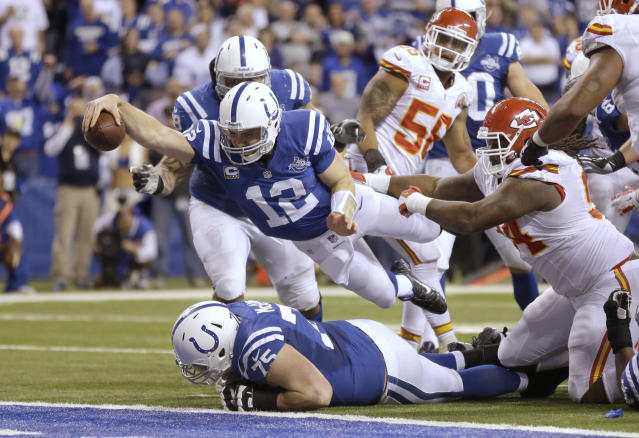 Indianapolis Colts quarterback Andrew Luck (12) dives for a touchdown after recovering a fumble by the Colts' Eric Berry during the second half of an NFL wild-card playoff football game against the Kansas City Chiefs Saturday, Jan. 4, 2014, in Indianapolis. (AP Photo/Michael Conroy)