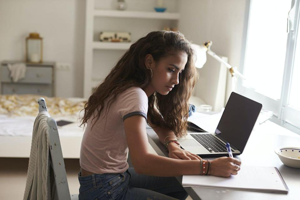 A girl sits at a desk in front of her laptop and writes on a notepad