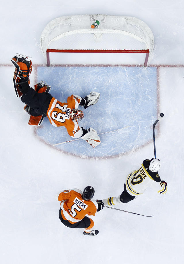 Boston Bruins' Anders Bjork, right, takes a shot to score a goal past Philadelphia Flyers goaltender Carter Hart (79) as Philippe Myers defends during the first period of an NHL hockey game, Monday, Jan. 13, 2020, in Philadelphia. (AP Photo/Derik Hamilton)