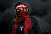 A protester covers her face with a scarf as she blocks a main highway during a protest in the town of Zouk Mosbeh, north of Beirut, Lebanon, Monday, March 8, 2021. The days-long protests intensified Monday amid a crash in the local currency, an increase of consumer goods prices and political bickering between rival groups that has delayed the formation of a new government. (AP Photo/Hussein Malla)