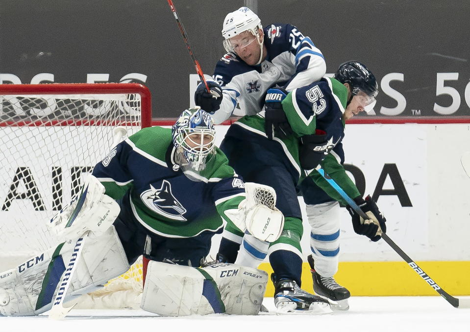 Vancouver Canucks center Bo Horvat (53) tries to clear Winnipeg Jets center Paul Stastny (25) from getting a shot against Canucks goaltender Braden Holtby (49) during second-period NHL hockey game action in Vancouver, British Columbia, Sunday, Feb. 21, 2021. (Jonathan Hayward/The Canadian Press via AP)