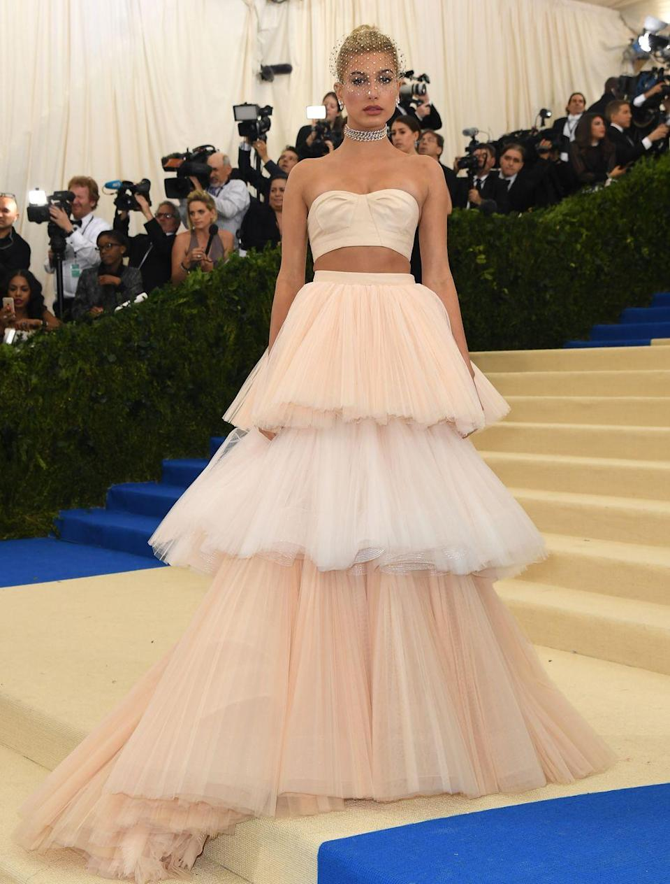 "<p>Hailey Baldwin<span class=""redactor-invisible-space""> wore a Carolina Herrera crop top and matching tiered tulle skirt to attend the 2017 Met Gala.</span></p>"