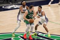 Sacramento Kings' Marvin Bagley III, left rear, and Justin James, right, defend as Dallas Mavericks guard Luka Doncic (77) advances the ball in the second half of an NBA basketball game in Dallas, Sunday, May 2, 2021. (AP Photo/Tony Gutierrez)