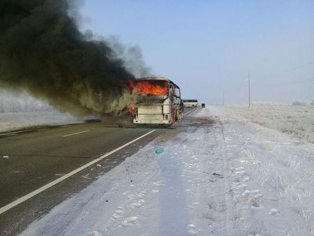 A view shows a burning bus on a route used by migrant workers heading to Russia, in the Aktobe region