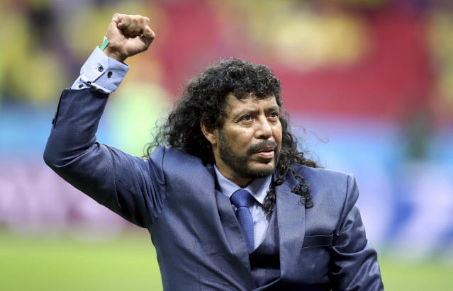 Rene Higuita, former goalkeeper of the national team of Colombia, raises a fist prior to the group H match between Poland and Colombia at the 2018 soccer World Cup at the Kazan Arena in Kazan, Russia, Sunday, June 24, 2018. (AP Photo/Thanassis Stavrakis)