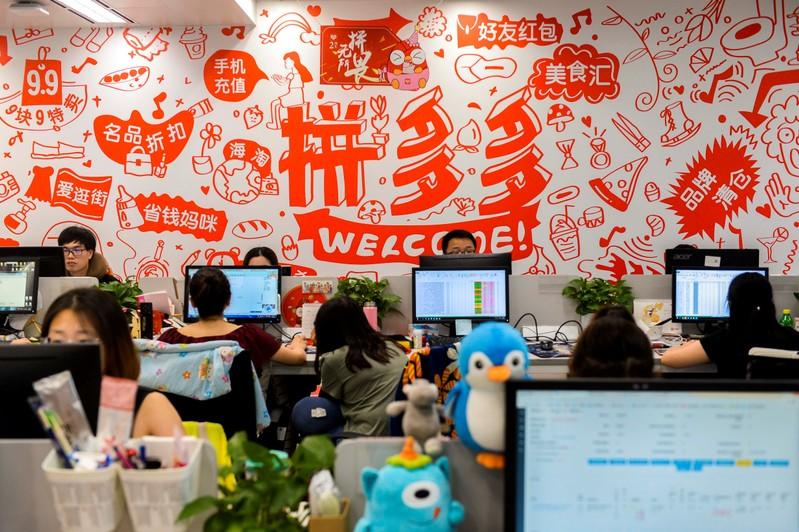 FILE PHOTO: People are seen at their desks at the headquarters of Chinese online group discounter Pinduoduo in Shanghai